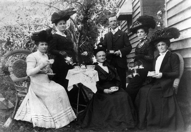 Skupina ľudí si vychutnáva anglický čaj o piatej
