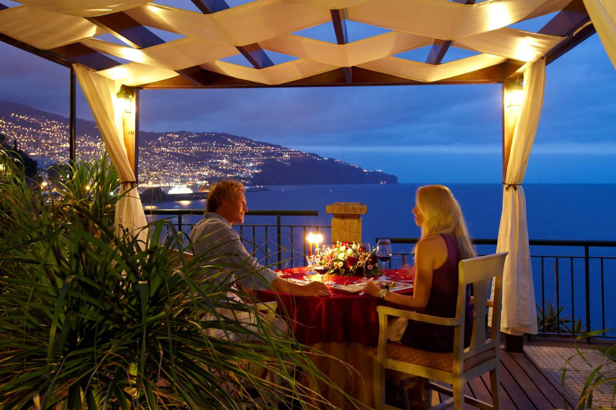 Muž so ženou večerajú na brehu mora