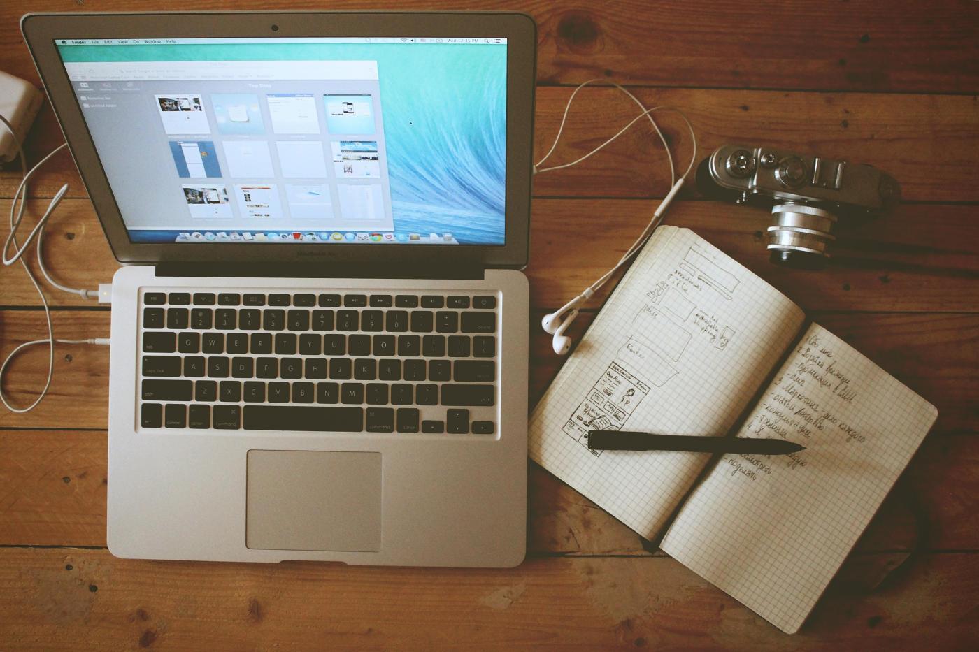 Zápisník, fotoaparát a Macbook ležiaci na stole