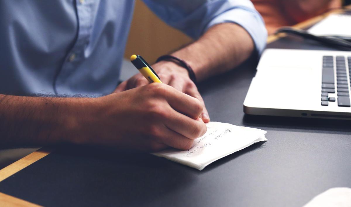 Muž si píše poznámky do svojho zápisníka