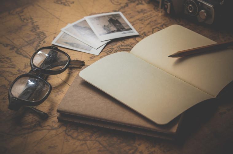 Zápisník a okuliare ležiace na stole