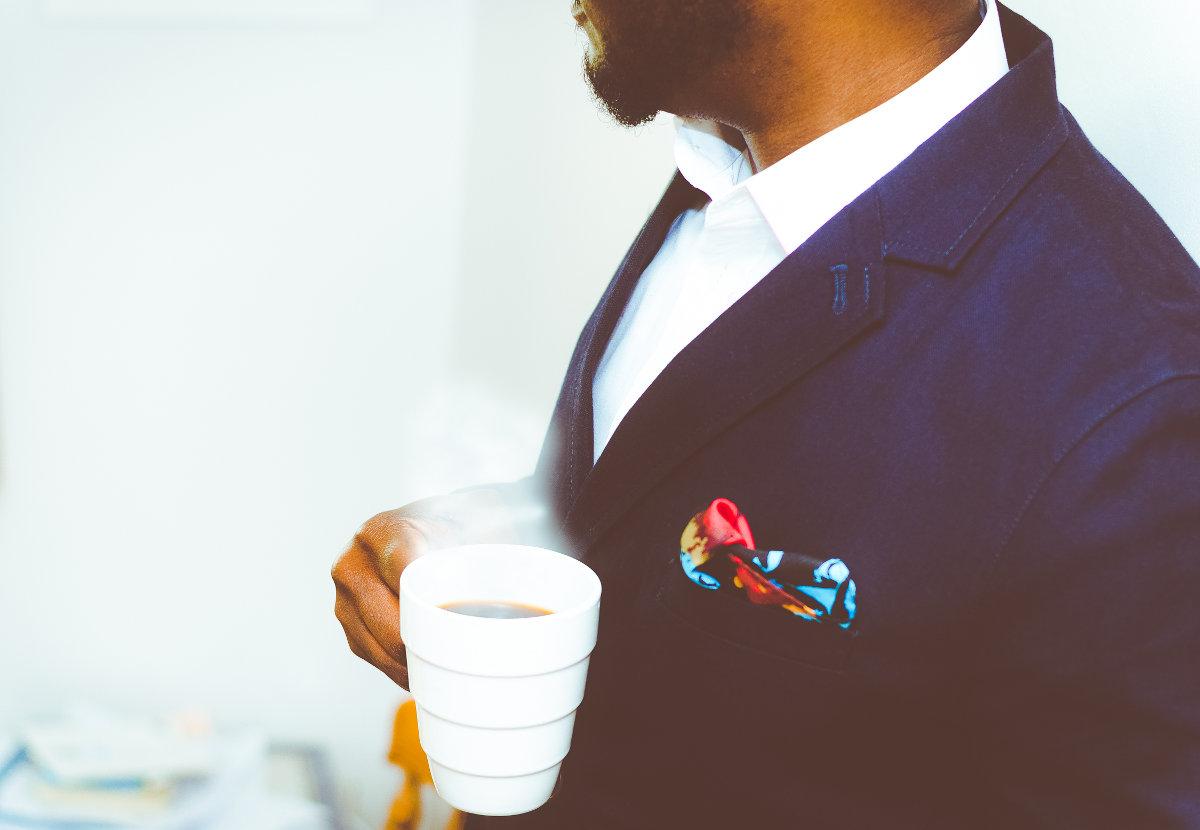 Muž v saku pije kávu