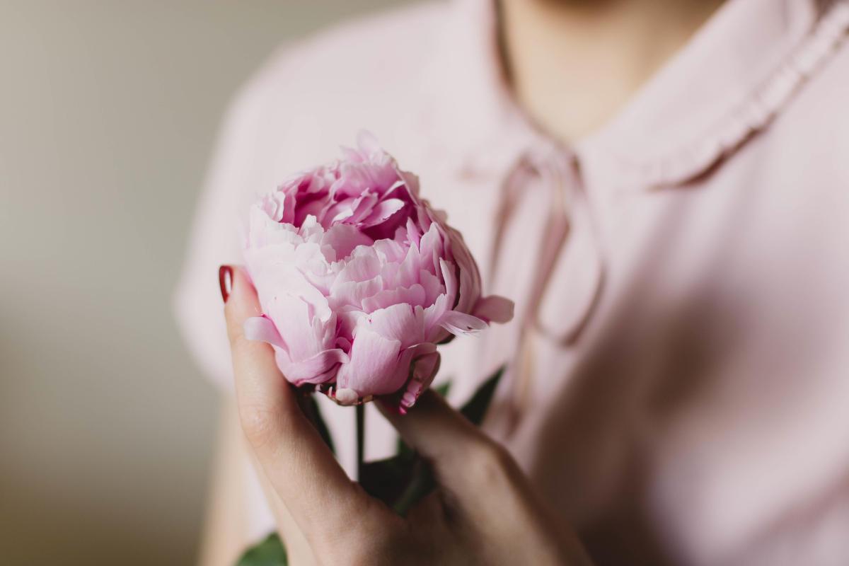 Žena sa teší z darovaného kvetu